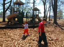 Autumn Park. Young children walk around a leaf covered park on a beautiful afternoon Stock Photo