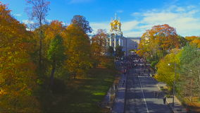 Autumn Park the alley in Pushkin, Russia. Camera flies along the alley on which people walk, to the left of the Avenue are red in the trees, and in the end stock video