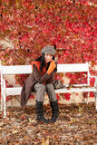 Autumn park bench young woman relaxing Stock Image