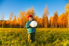 Autumn park and boy with ball. Laughing three years old little boy holding white volleyball ball autumn park royalty free stock photography