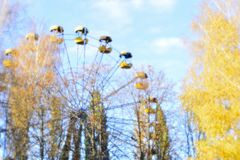 Autumn Park, Ferris wheel the bottom view, the foreground trees with yellow leaves. Blur. Photography soft lens royalty free stock photo