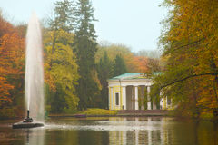 Autumn park  lake with a fountain scene. Ancient like pavilion in park lake with fountain in autumn Royalty Free Stock Photo