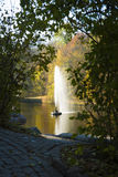 Autumn park lake with a fountain. Seen through dense foliage Royalty Free Stock Photography