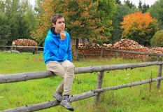 Teenage boy sitting on a fence. In the countryside, thinking about something Royalty Free Stock Images