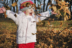 Autumn in the park Little girl throws yellow leaves. Royalty Free Stock Images