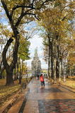 Autumn park and a monument. To Volodymyr the Great, trees and fallen leaves, people walking after rain. Kiev, Ukraine Stock Photo