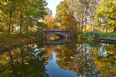 Autumn park - a pond with a picturesque bridge. Autumn landscape - a park in golden colors, a picturesque pond with trees reflecting in the mirror, its banks stock images