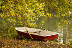 Autumn park with red boat in the pond Royalty Free Stock Photos