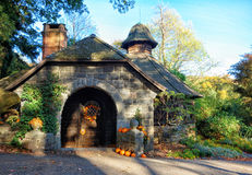 Autumn Park. Small decorative stone house in autumn park. Shrubs, trees, flowers, pumpkins stock images