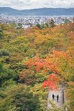 Autumn park view from above with Kyoto cityscape in the distance. People walking in the park surrounding the famous Kiyomizu-dera buddhist temple in autumn royalty free stock photo