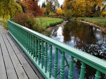 Autumn park with white swan swimming by pond , view from behind bridge railing stock photos