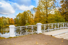 Autumn park with white wooden bridge. And openwork fence in Pushkin, Tsarskoe Selo, St. Petersburg, Russia, 2015 Royalty Free Stock Photos