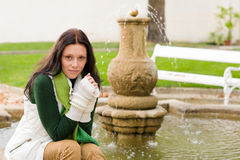 Autumn park young woman sit on fountain Royalty Free Stock Photo