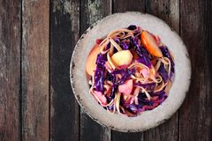 Autumn pasta dish with apples, purple cabbage on rustic wood Royalty Free Stock Photos
