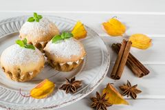 Autumn pastries. Homemade cupcakes with powdered sugar with cinnamon sticks, anise stars Royalty Free Stock Photo