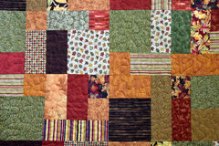 Autumn patchwork quilt background. Autumn print fabric design of a homemade patchwork quilt Royalty Free Stock Photo