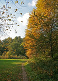 Autumn path. A path in autumn park coming out into the clearing Royalty Free Stock Photo