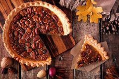 Pecan pie with slice removed, table scene over wood. Autumn pecan pie, overhead table scene with cut slice on a rustic wood background royalty free stock photos