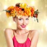 Autumn photo of young woman. Beauty portrait of smiling young attractive woman with autumn flowers on head. Conceptual photo stock photography