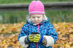 Autumn picnic portrait of little girl holding and looking at steel thermos flask cup Stock Photos