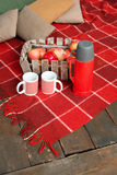 Autumn picnic on the terrace. Red plaid, basket with apples and thermos with hot drink. Veranda of countryside house in. Autumn season Stock Photo