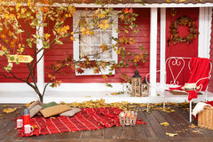 Autumn picnic on the terrace. Red plaid, basket with apples and thermos with hot drink. Veranda of countryside house in. Autumn season Royalty Free Stock Photography