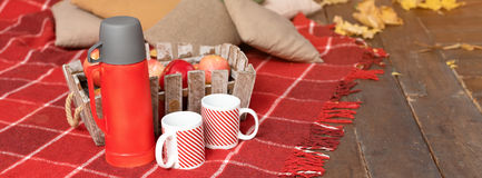 Autumn picnic on the terrace. Red plaid, basket with apples and thermos with hot drink. Veranda of countryside house in. Autumn season. Banner for website Stock Photography