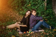 Autumn picnic, a young beautiful couple in the woods. A man and a woman sitting on a blanket royalty free stock photography