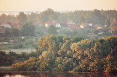 Autumn pictorial landscape with small village in the forest near the river. In early morning. Soft filter and vintage tones processing. Aerial view Royalty Free Stock Photos