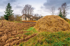 Autumn plowed field with trees, house and haystack Stock Image