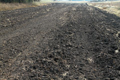 Autumn plowed strip of land. Preparing for winter in the village. Or on a farm Royalty Free Stock Image