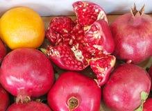 Autumn Pomegranates e uma laranja indicada em um mercado dos fazendeiros Imagens de Stock Royalty Free