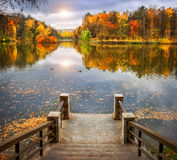 Autumn pond. With gold and red trees and a small pier Stock Photo