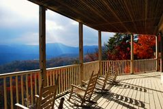 Autumn porch and fall colors. Autumn view of mountains and valley from the front porch with rocking chairs and fall colors in view during early morning sunlight Royalty Free Stock Photo