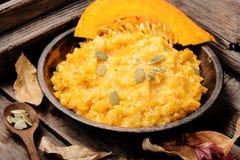 Autumn porridge with pumpkin. Homemade tasty porridge with orange pumpkin on rustic background.Healthy vegetarian meal royalty free stock photography