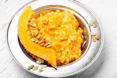 Autumn porridge with pumpkin. Homemade tasty porridge with orange pumpkin on white background.Healthy breakfast royalty free stock images
