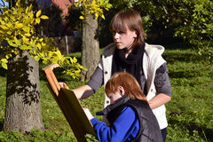Autumn portrait. Female painter and kid drawing in a city park Stock Photography