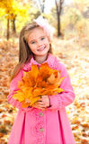 Autumn portrait of adorable little girl with maple leaves Royalty Free Stock Photo