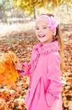 Autumn portrait of adorable little girl with maple leaves Stock Photos
