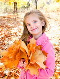Autumn portrait of adorable little girl with maple leaves Royalty Free Stock Photography