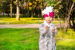 Autumn portrait of beautiful child. Happy little girl with leaves in the park in fall. stock photo