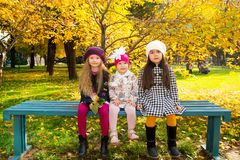 Autumn portrait of beautiful children on the bench. Happy little girls with leaves in the park in fall. royalty free stock image