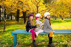 Autumn portrait of beautiful children on the bench. Happy little girls with leaves in the park in fall. stock photography