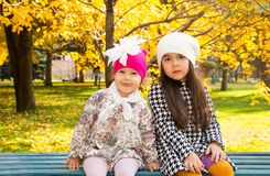 Autumn portrait of beautiful children on the bench. Happy little girls with leaves in the park in fall. Stock Photo