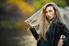 Autumn portrait of beautiful girl against the lake stock image