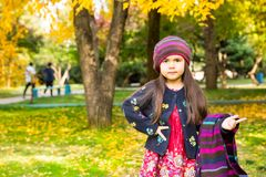 Autumn portrait of beautiful kazakh, asian child. Happy little girl with leaves in the park in fall. Autumn portrait of beautiful child. Happy little girl with Royalty Free Stock Images