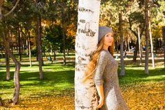 Autumn portrait of beautiful woman over yellow leaves while walking in the park in fall. Positive emotions and happiness concept. Autumn portrait of a beautiful Stock Images