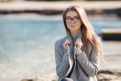 Autumn portrait of a beautiful woman on the sea shore Royalty Free Stock Images
