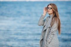 Autumn portrait of a beautiful woman on the sea shore Stock Photo
