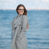 Autumn portrait of a beautiful woman on the sea shore Stock Images